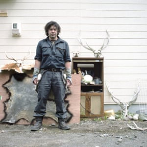 Monbetsu, a professional deer and bear hunter, photographed outside his home with his hunting trophies. Hunting is a tradition still widely practiced among the Ainu.