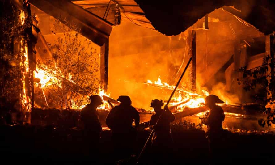 Firefighters tend to a structure lost during the Kincade fire east of Healdsburg, California.