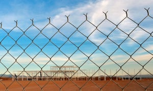 a wire fence and a derelict building site on red sand