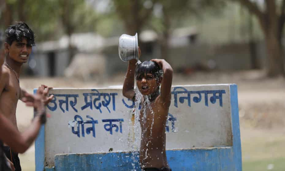 Indian boys bath at a drinking water tap on a hot day in Prayagraj, India.