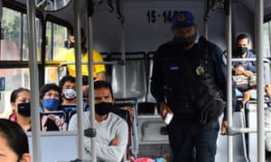 Officers check people's temperatures on bus passengers at a checkpoint in Mexico City.