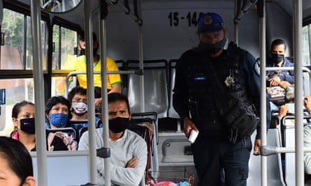 Officers check temperatures of bus passengers at a checkpoint in Mexico City.