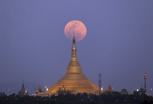 On the rise, the moon is photographed moving behind the Uppatasanti Pagoda, in Naypyitaw, Myanmar