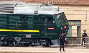 Police officers keep watch next to a train at the Beijing railway station.