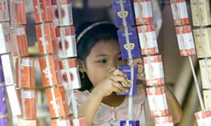A Cambodian girl prepares a cigarette display. In Cambodia 44.1% of adult males smoke.