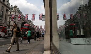 Shoppers walk under union flags hanging above Regent Street in central London
