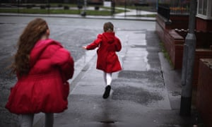 Two girls running down the street away from the camera