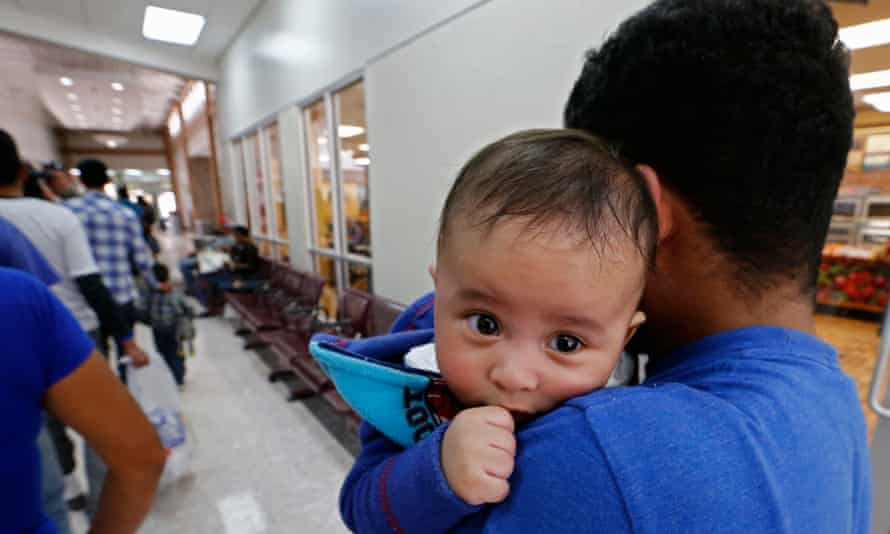 Migrant families enter to be processed at a bus station on 29 June, in McAllen, Texas. The administration faces a deadline of reuniting 2,000 older children with their families by 26 July.