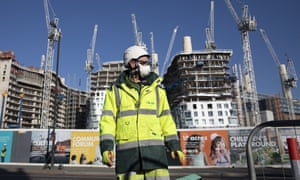 worker wearing a mask in front of a construction site