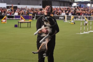 A woman celebrates with her dog after participating in the Masters Agility Championship