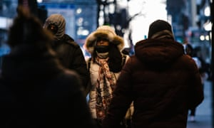 People walking in the street in New York, bundled up in coats and hats