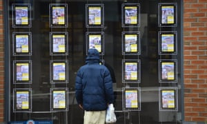 A man is seen looking at houses for sale at Butter Jon Bee's estate agents in Stoke-on-Trent, Staffordshire.