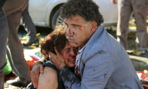 An injured man hugs an injured woman after the explosion