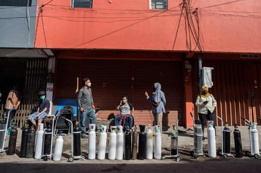 Warga mengantre untuk mengisi tangki oksigen di sebuah stasiun pengisian bahan bakar di Surabaya, kota terbesar kedua di Indonesia.