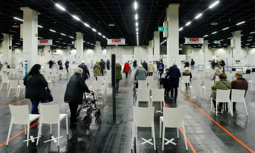 People wait to receive a Covid vaccine at a centre temporarily set up in a trade fair hall in Cologne.