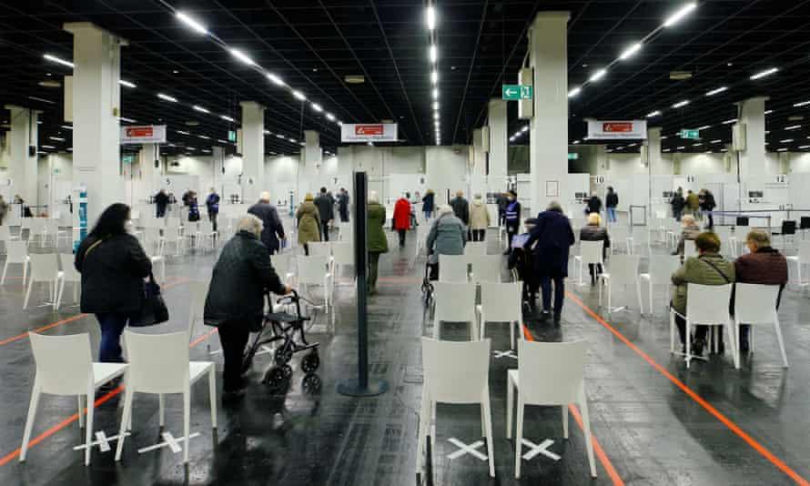 مردم منتظر دریافت واکسن Covid در مرکزی هستند که به طور موقت در سالن نمایشگاه های تجاری در کلن تاسیس شده است.