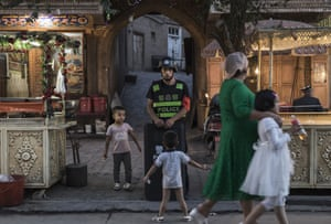 Uyghur children joke as they taunt a local police officer