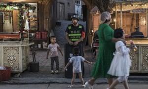Uighur children pass a policeman