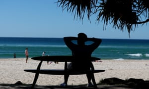 A man sits on a bench at Burleigh Heads on Saturday doing something he would not have been allowed to do the day before.