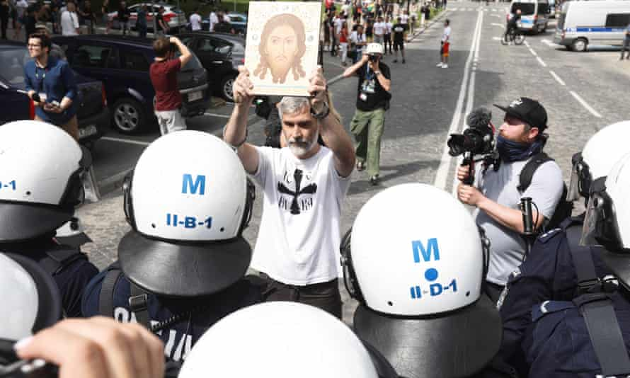 A man displays an image of Christ to mark his anti-Pride feelings.