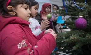 Refugee children decorate a tree