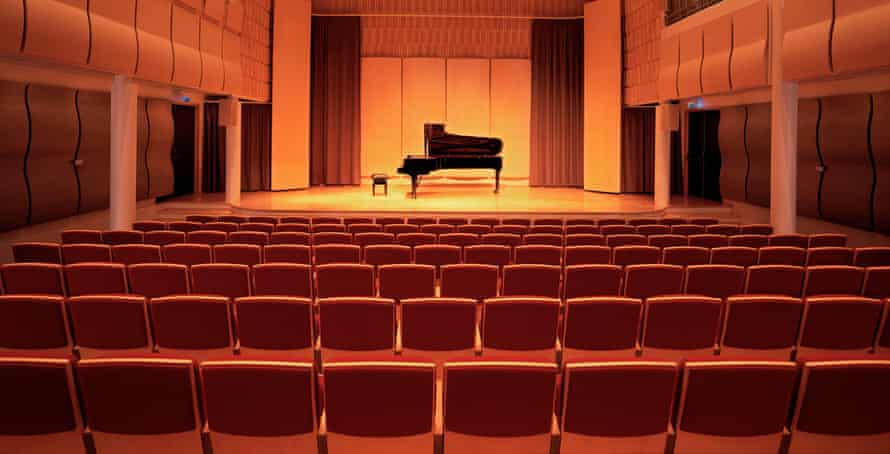A piano on stage inside an empty concert hall
