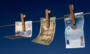 Twenty pounds, dollars, euro banknotes hanging on a washing line