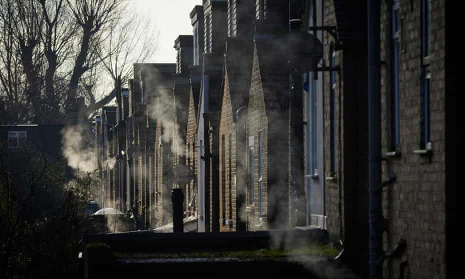 The backs of a row of Victorian terraced houses, lit weakly by the sun through the branches of bare trees, with clouds of smoke from numerous gas boiler exhausts visible all along the row