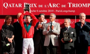Pierre-Charles Boudot holds up the Arc trophy on the podium with winning trainer Andre Fabre, second right.