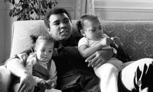 Ali cuddling his daughters Laila, (L )and Hana (R) at a Hotel in London.