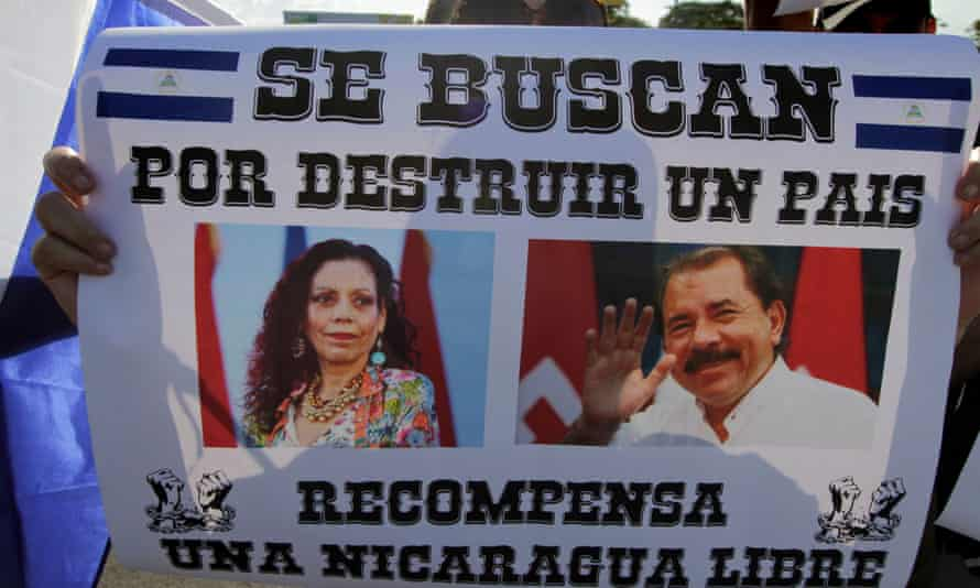 A demonstrator holds a poster depicting Nicaraguan President Daniel Ortega and his wife Vice-President Rosario Murillo reading 'Wanted for destroying a country. Reward: A Free Nicaragua'.