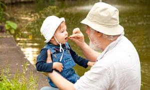 Grandchild and grandfather having fun outdoors.