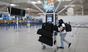 A passenger walks through departures at Stansted in June.