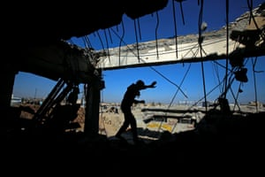 An Iraqi runs through a destroyed building as Iraqi forces battle with Isis militants in western Mosul