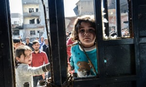 A girl looks at a dead body among the rubble of damaged buildings in Cizre.