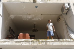 A man looks out of the collapsed facade of an apartmen