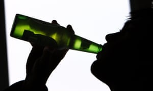 Silhouette of man drinking from bottle of beer