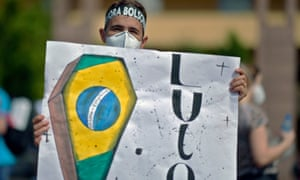 A man wearing a headband reading 'Bolsonaro out' holds a sign depicting a coffin with the Brazilian flag reading 'Mourning' during a protest against Brazilian president Jair Bolsonaro's handling of the pandemic in Belo Horizonte, Brazil.