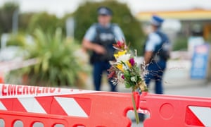 Flowers are seen in front of a police cordon at Linwood mosque.