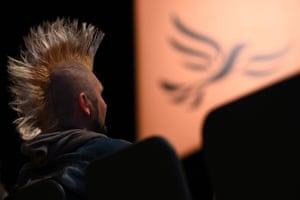 Bournemouth, UK: A man sporting a mohican haircut listens to speeches during the Liberal Democrat party conference