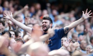 Manchester City fans celebrate after Rodri scores their fourth goal.