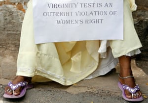 A protester holds a placard during a protest against virginity tests in New Delhi, India