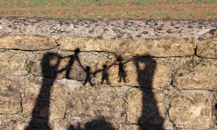 Family paper chain of people / dolls shadows / silhouettes against wall