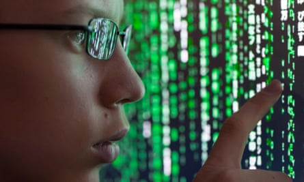A young man with glasses is watching futuristic symbols on a computer screen. Symbols are reflecting in the man's glasses.
