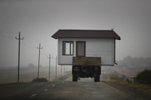 A family drives a truck loaded with a small house along a highway as they leave their village in the separatist region of Nagorno-Karabakh.