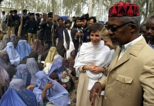 Annan, wearing a traditional Afghan cap, talks to veiled Afghan refugee women at Shamshato refugee camp near Peshawar, north-west Pakistan in 2001