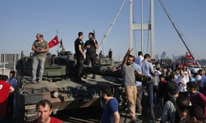 People gather around police officers loyal to the government standing atop tanks abandoned on the Bosphorus Bridge after the coup attempt