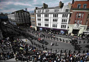 The cortege passes a line of police officers and well-wishers