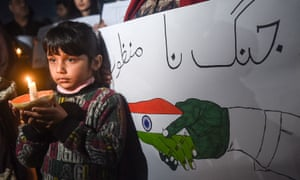 A Pakistani girl holds a light candle during a vigil for peace in Lahore