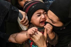 Lahore, Pakistan. A child cries as a health worker administers an injection during a polio vaccination campaign